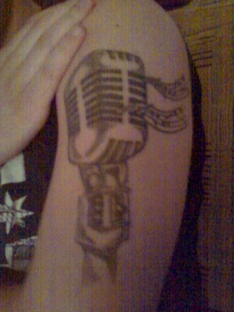 John Laszkow's fourth tattoo of a microphone drawn up by his friend Amy and done by Jay Herring at his home in New Jersey.